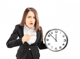 Angry young businesswoman pointing on a wall clock