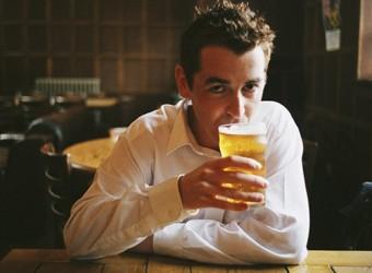 Man drinking pint of beer in pub