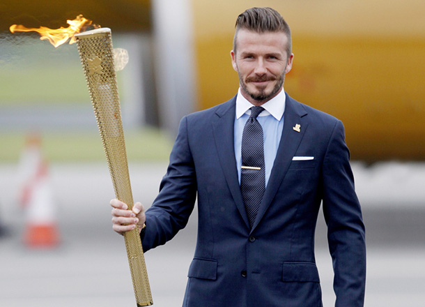 epa03224589 Soccer player David Beckham holds a torch as he arrives from Athens, Greece with The London 2012 Olympic Games Flame at Royal Naval Air Station (RNAS) Culdrose near Helston, Cornwall, Britain, 18 May 2012.The 8,000 mile, 70-day torch relay around the UK begins on 19 May.  EPA/TAL COHEN