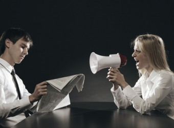 Girl with megaphone, shouting loudly, young man is reading a newspaper ignoring her