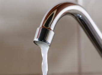 Horizontal image of a tap with water flowing slowly during a period of scarcity