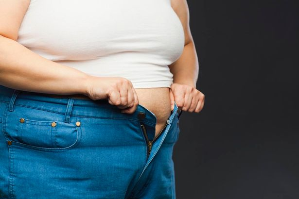 Overweight-woman-trying-to-do-up-jeans