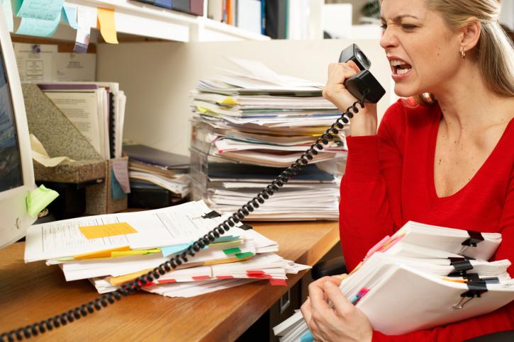 Female office worker holding paperwork, snarling at phone handset